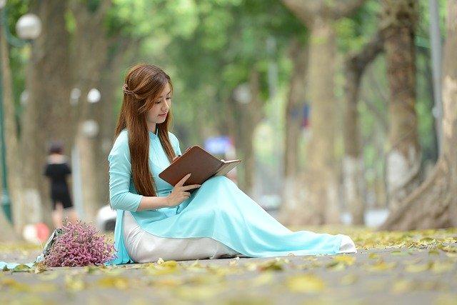 Chica vietnamita leyendo en el parque